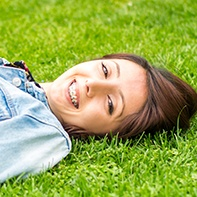 Teen with braces laying outside