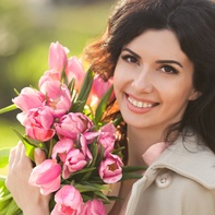 Smiling woman with braces holding flowers