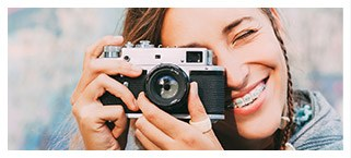 Young woman with braces looking through camera lens