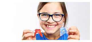 Young girl holding two retainers