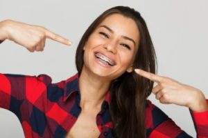 Smiling woman pointing at her braces