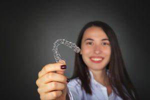 girl holding Invisalign