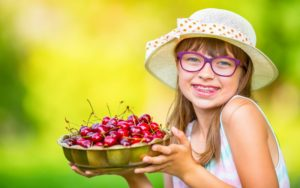 young person with braces holding a bowl of cherries
