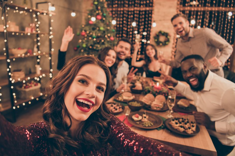 Woman with Invisalign smiling with her family during holidays