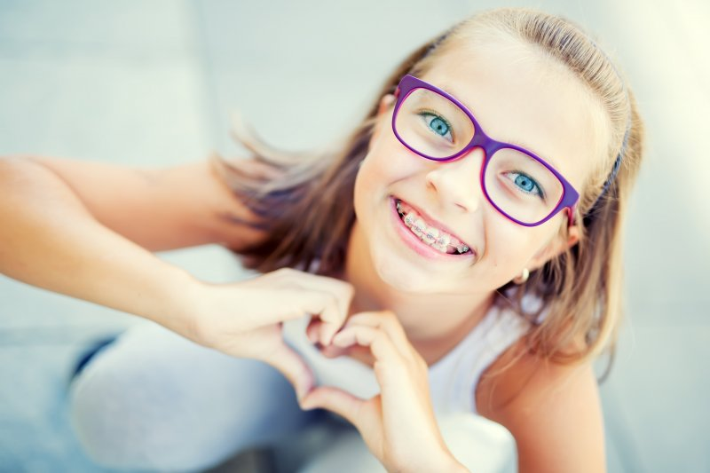 a young girl wearing purple glasses and braces makes a heart with her hands